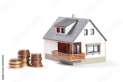 Finance and house expenses or investing concept. Home with coins