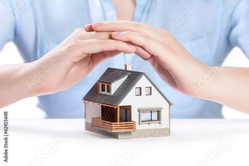 Insurance and house protection concept. House under womans hand