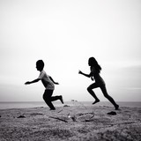 two kids running silhouettes running on the beach