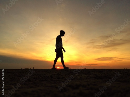 man silhouette walking on the beach