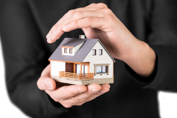 Home Insurance and protection concept. Home in man's hand