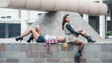 Two girls portrait sit outdoors with modern building as backgrou