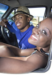 Black couple sit in car , beach