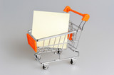 Blank paper sheet in shopping cart on gray