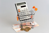 Calculator in shopping cart situated on banknotes on gray