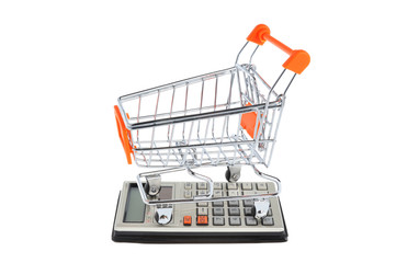 Shopping cart situated on calculator isolated on white