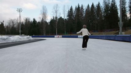 woman figure skating at an open outdoor speed skating rink rear