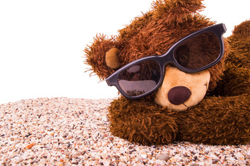 Teddy bear is sunbathing with beachsand