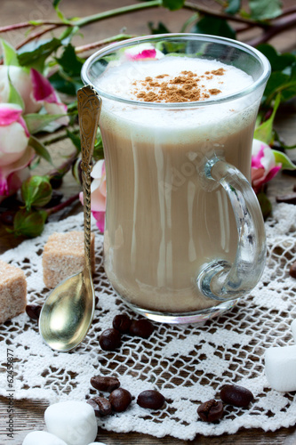 coffee latte with cinnamon on lace serviette
