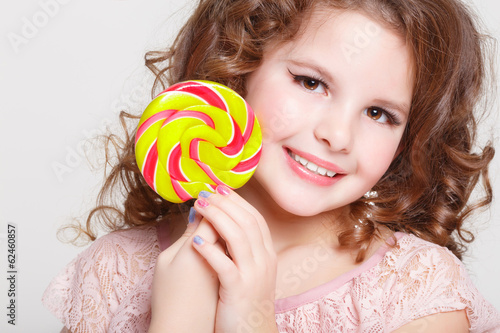 Funny child with candy lollipop Funny baby girl eating sweets