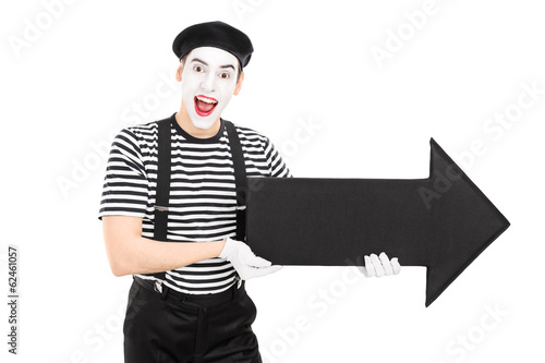 Male comedian holding a big black arrow pointing right