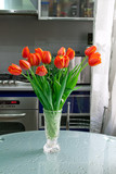 Tulips in the vase at the table on the kithen background