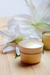 Face care and spa concept - face cream and lily flowers