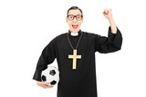Male reverend holding football and raising a fist