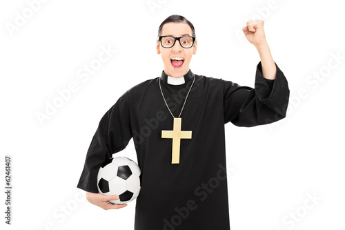 Male reverend holding football and raising a fist - 62461407