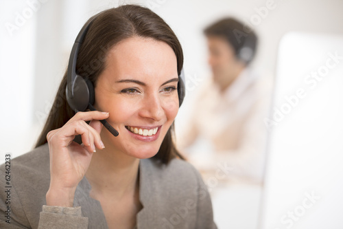 Helpline operator with computer in office, headset