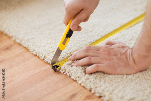 close up of male hands cutting carpet