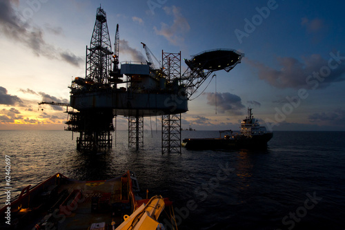 canvas print picture Silhouette of offshore jack up rig at sea during sunset