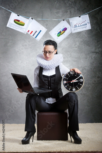 Business lady in ruff collar with a clock using laptop