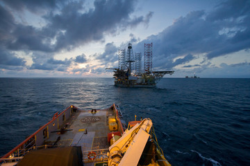 An offshore vessel towing the oil and gas platform during sunset