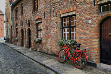 Red bicycle near the window of brick house in Brugge, Belgium.