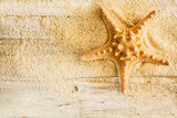 Spiny starfish and sea sand on wooden boards
