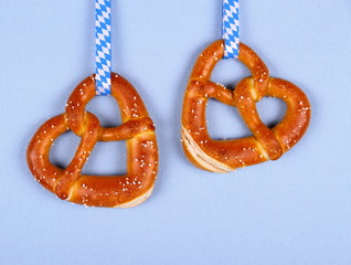 Two pretzel in heart shape on blue background
