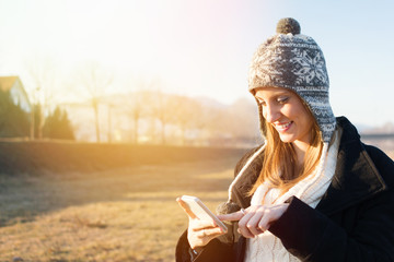 Young student woman using smartphone outdoors