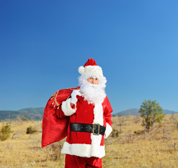 Santa in the middle of nowhere with bag of presents