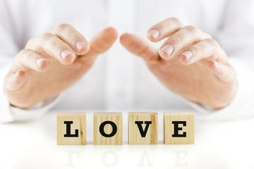 Man holding protective hands above the word Love