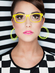 Attractive young woman wearing glasses on stripy background