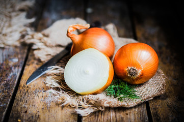 Golden onions on rustic wooden background