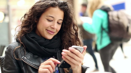 Attractive young woman using a smart phone and smiling
