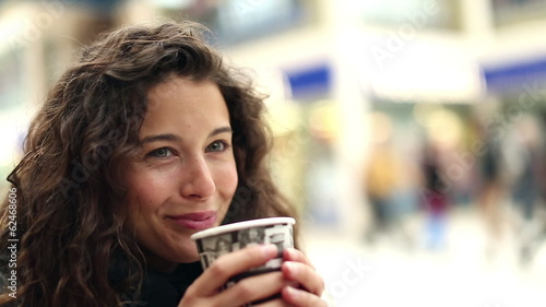 Attractive young woman having a hot drink and smiling to herself
