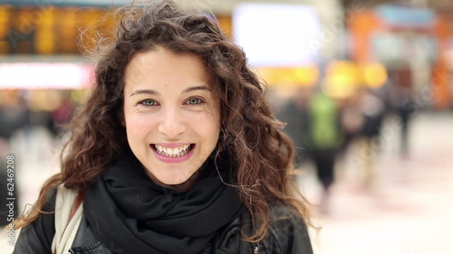 Portrait of a young happy woman smiling at a station