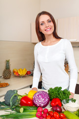 happy young woman with vegetables at kitchen