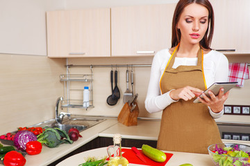 woman using a tablet computer to cook in her kitchen
