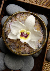 Bowl of spa salt with stones with orchid on mat