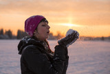 Girl blows snow with hands on sunset background