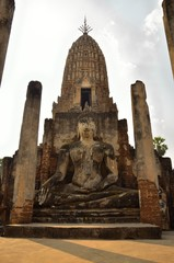 Buddha sitting in front of ruin pagoda