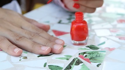 Nail polish that is red  is painted on her fingernails
