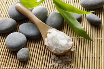 spoon with stones on bamboo stick straw mat