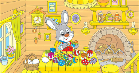 Rabbit coloring Easter eggs to the holiday