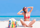 young woman in bikini and sunglasses with beach bag sitting on