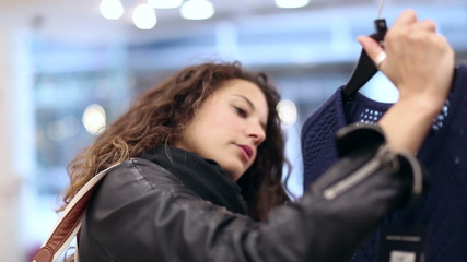 Attractive young woman browsing at clothes in a shop