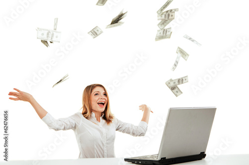 Young woman with laptop and flying money. Isolated