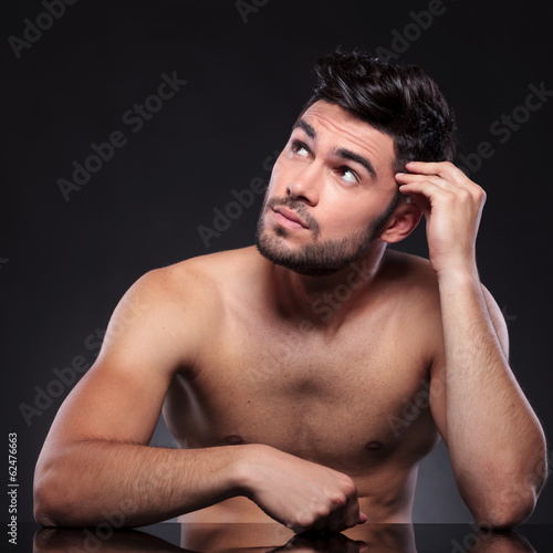 naked young man looks up