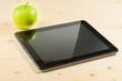 digital tablet pc near green apple on wood table