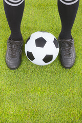 Soccer player's feet  and football on field