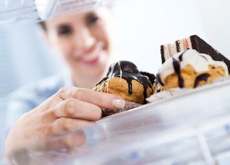 Woman picking pastries in the refrigerator.